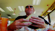 Stock Video Footage of Man Eating Burrito At Fast Food Restaurant- Fast Motion