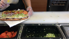Putting toppings at sub at restaurant Stock Footage