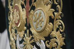 Embroidery thread of gold on green velvet with the acronym for christ and mar Stock Photos