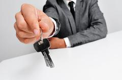 Man in suit giving the keys Stock Photos
