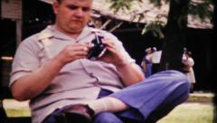 670 - a photographer adjust his camera for next shot - vintage film home movie Stock Footage