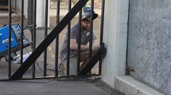 MAN FIXING WELDING A GATE OUTSIDE Stock Footage