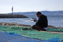 sailor fixed their fishing nets in the port of estepona, province of malaga,  - stock photo