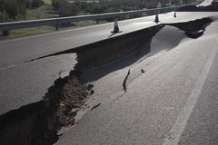 Asphalt road with a crack caused by landslides Stock Photos