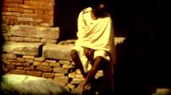 Culture Nepal Kathmandu Man Sitting on a Wall in a Robe poverty Stock Footage