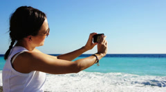 Young woman taking photograph by cellphone on sea beach HD Stock Footage