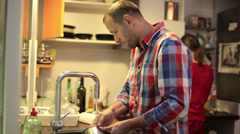 Young man doing dishes after diner in the kitchen at home HD Stock Footage
