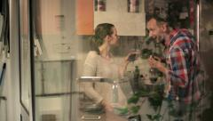 Happy couple talking and drinking wine in kitchen at home HD Stock Footage