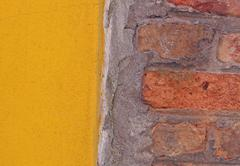 Yellow wall in contrast to the red brick Stock Photos