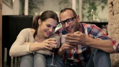 Couple drinking wine and watching funny things on smartphone HD Stock Footage