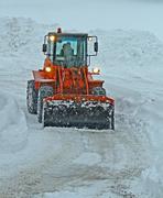 Oranssi lumiaura tyhjentää kaduilla aikana lumimyrsky Kuvituskuvat