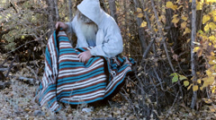 Homeless man sitting in trees with blanket HD 0149 Stock Footage