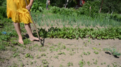 Barefoot woman in yellow dress grub weeds with hoe in garden Stock Footage
