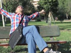 Young man relaxing and streching, sitting on the bench in park NTSC Stock Footage