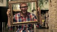 Stock Video Footage of Man changing his emotions behind picture frame from sad to happy HD