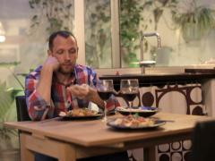 Worried young man drinking red wine and waiting with the dinner NTSC Stock Footage