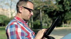 Young man browsing on tablet sitting on bench in the park HD - stock footage