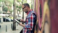 Stock Video Footage of Young trendy hipster with tablet computer stand by graffiti wall HD