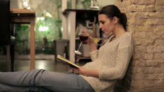 Young woman reading book, drinking wine at home HD Stock Footage