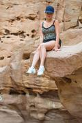 Girl sitting on a rock Stock Photos