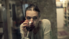 Beautiful sad woman drinking wine by the window at home HD Stock Footage