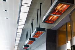 electric heater with halogen coils at front gate of hotel - stock photo