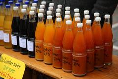 Very fresh apple juice  and elderberry juice in glass bottles - stock photo