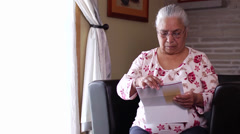 Senior latino woman can't understand her bills. Stock Footage