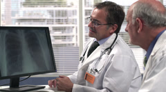 Two male doctors looking at an x-ray - stock footage