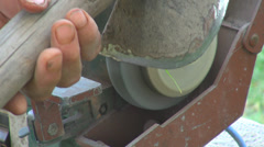 Worker holding blade hoe grindstone grinding spark traditional tool sharpening  Stock Footage