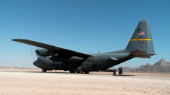 Loading supplies and cargo into a C-130 Hercules transport plane Stock Footage