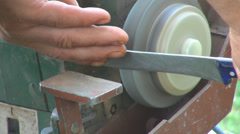 Worker holding blade knife grindstone grinding spark traditional tool sharpening Stock Footage