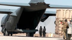 Loading supplies and cargo into a C-130 Hercules transport plane - stock footage