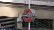 Stock Video Footage of London Underground symbol long shot with pedestrians passing