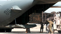 Forklift Loading supplies and cargo into a C-130 Hercules transport plane - stock footage
