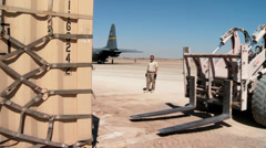 A forklift truck picks up a pallet to load on a C-130 Hercules Stock Footage