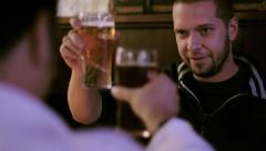 Two men toasting beer in a pub Stock Footage