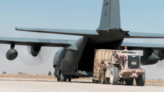 Stock Video Footage of Forklift truck Loading supplies and cargo into a C-130 Hercules transport plane