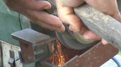 Worker holding blade axe grindstone grinding spark traditional tool sharpening  Stock Footage