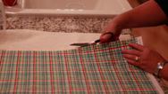 Stock Video Footage of a woman cuts fabric with scissors for advent calendar