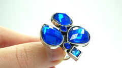 jewelery ring with blue sapphire crystals putting on the finger - stock footage
