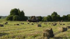 Farmers peasants load dried hay bales to tractor trailer Stock Footage