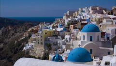 Santorini, Oia Old Town - Slow pan from rugged mountains to blue domed buildings Stock Footage