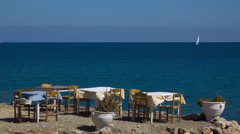 Plaka Elounda Crete Tables table cloths blowing in the breeze beside the sea Stock Footage