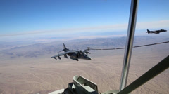 KC-130J Refuels Harrier AV-8B jump jet fighters in mid-air Stock Footage