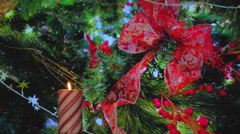 Holiday candy cane candle with red ribbon decorations - stock footage