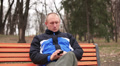 Adult evil  man talking on  mobile in  park. Front view Footage