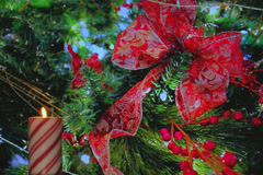 Holiday candy cane candle with red ribbon and decorations - stock footage