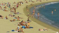 Spain Catalonia Barcelona beach swimmer sunbathing Stock Footage