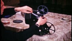 674 - man loading an 8mm movie projector - vintage film home movie Stock Footage